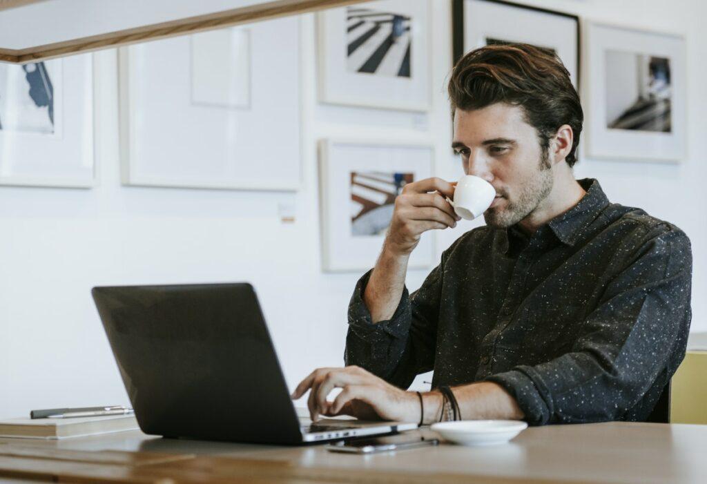 Hombre en su computadora buscando información sobre cómo construir su marca personal.