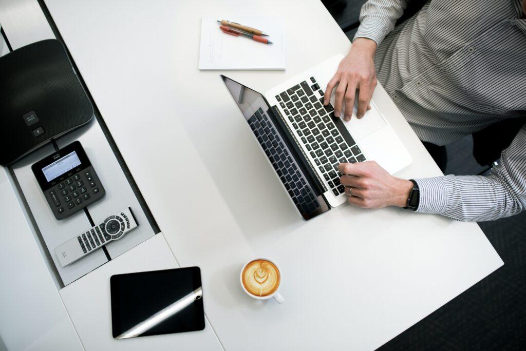 Hombre en su computadora buscando información sobre cómo escribir un guest post.