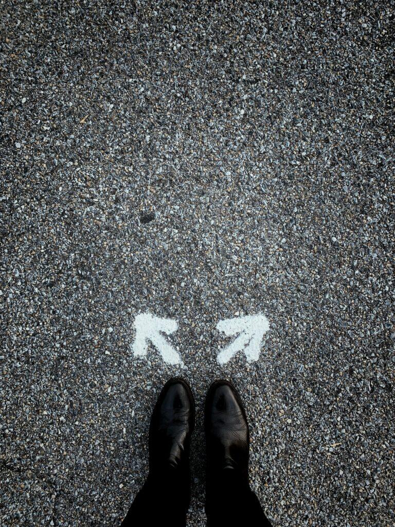 Hombre de pie sobre un piso de asfalto, en que se dibujan dos fechas en diferente dirección.