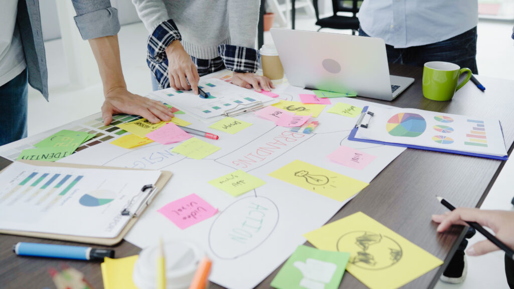 Grupo de trabajo en una oficina usando marcadores de colores para hacer un mapa conceptual sobre las relaciones públicas.