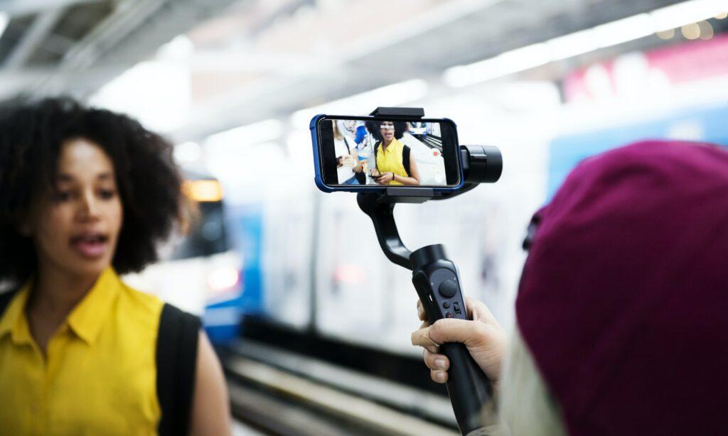 Mujer en la estación de metro grabando un video promocional para su página web
