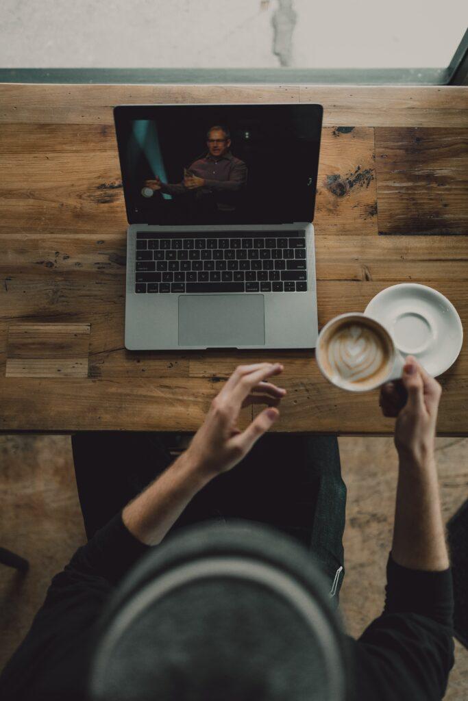 hombre bebiendo café mientras ve un video de marca.