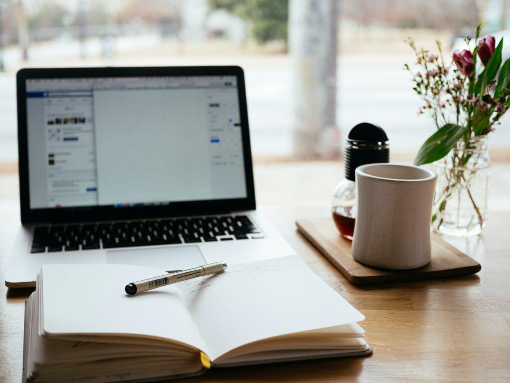 Una agenda en un escritorio en frente de un computador representando una estrategia de byline guest posting.