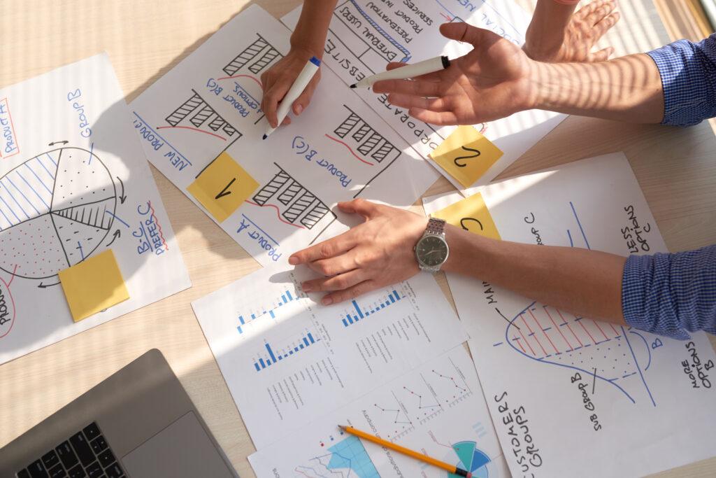 Grupo de trabajo dibujando esquemas y gráficas en carteleras para entender los beneficios de las relaciones públicas.