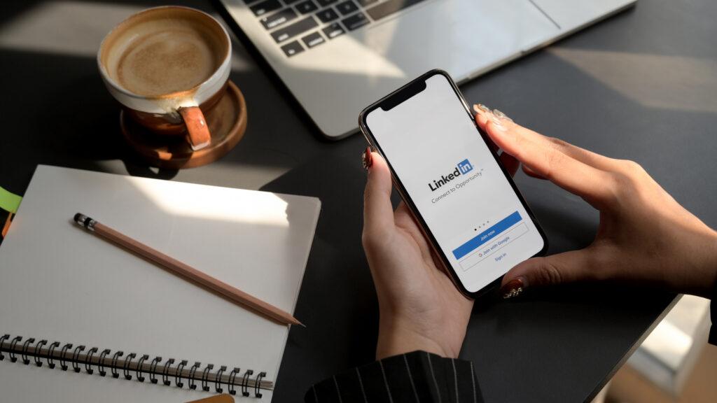 Mujer usando su telefono celular para crear una cuenta en LinkedIn y convertirse en una líder de opinión en línea.