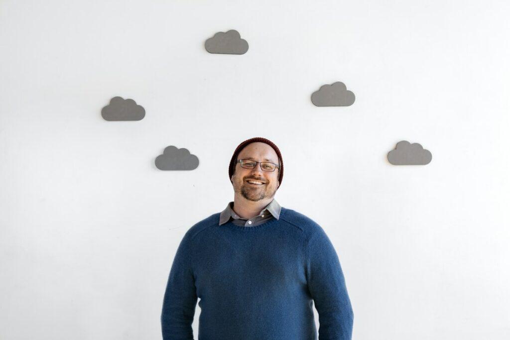 Hombre sonriente de frente en una pared blanca con nubes grises, representando a un líder de opinión.