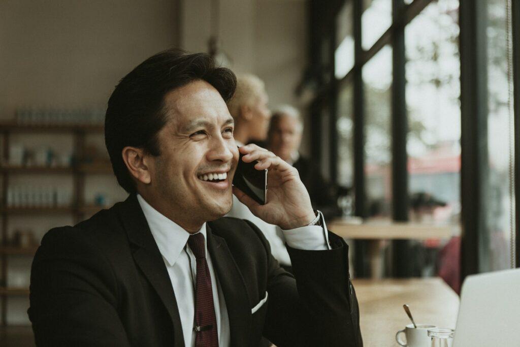 Hombre vestido de traje hablando en su teléfono celular sobre cómo convertirse en un líder de opinión.