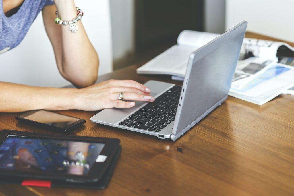 Mujer buscando información en su computadora sobre cómo optimizar contenido para SEO.