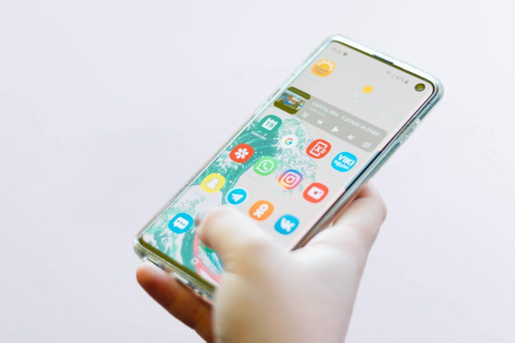 Mano de una persona que utiliza un teléfono celular para crear una marca comercial en línea.
