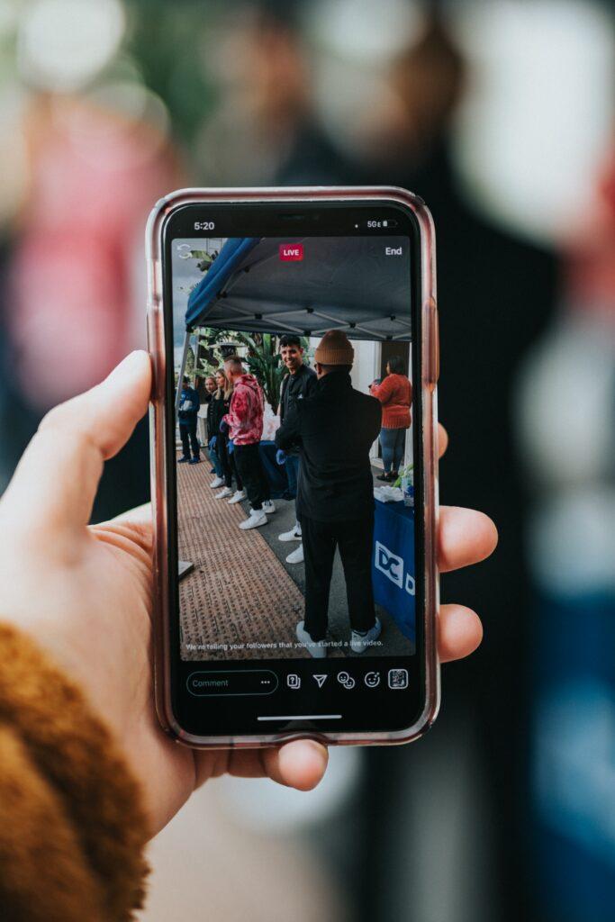 Hombre usando su teléfono celular para grabar videos promocionales.