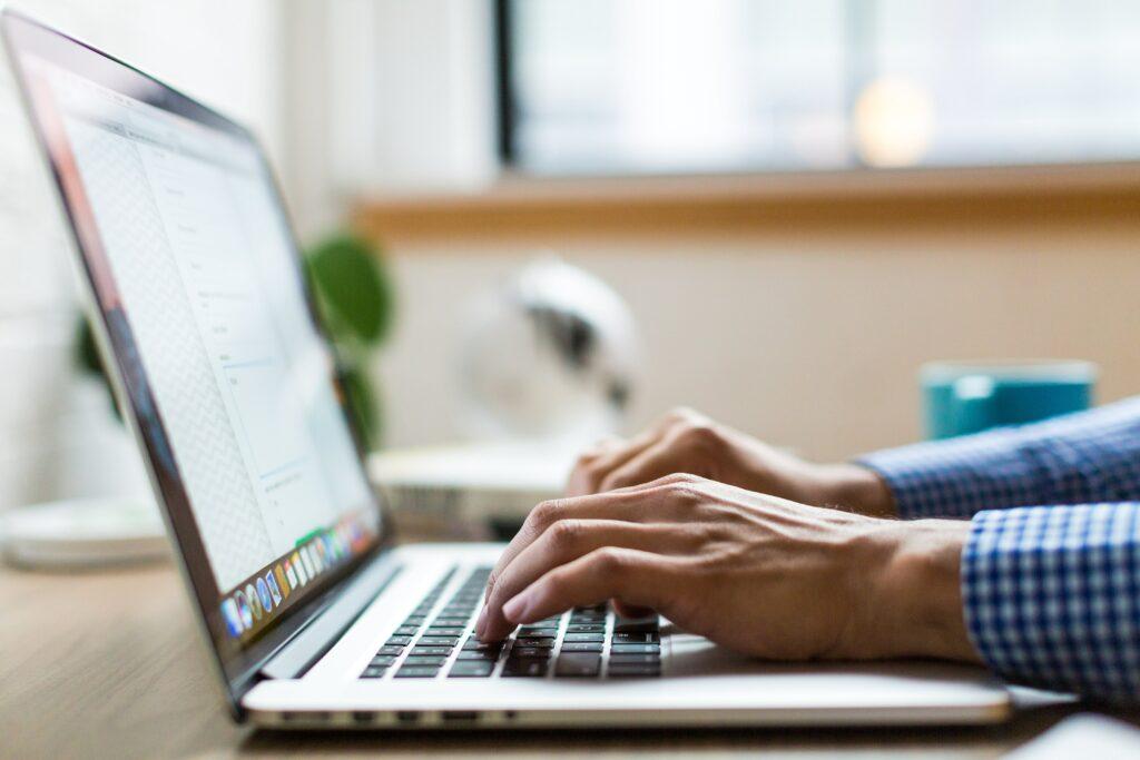 Hombre utilizando su computador para buscar información sobre Guest Posts